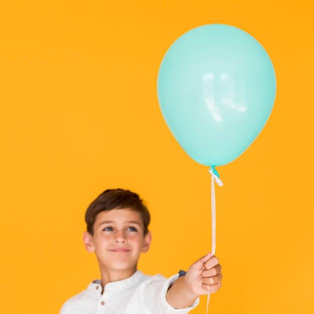 Glückliches kind, das einen blauen ballon hält Kostenlose Fotos