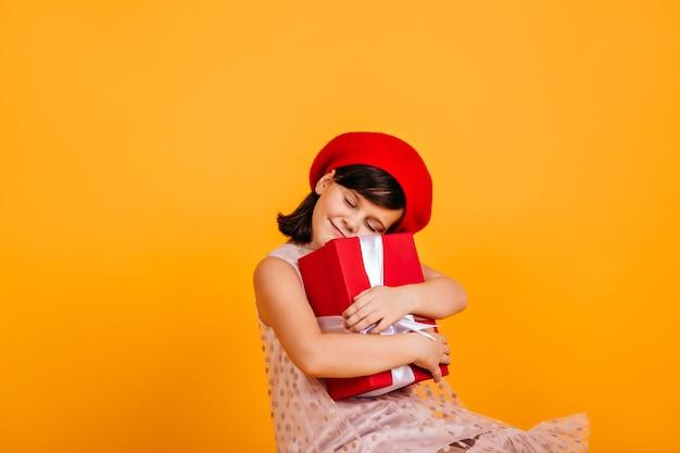 Glückliches kind, das geburtstagsgeschenk umarmt. fröhliches kleines mädchen mit geschenk. Kostenlose Fotos