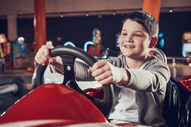 Glückliches kind, das im spielzeugauto in der unterhaltungsmitte sittng ist Premium Fotos