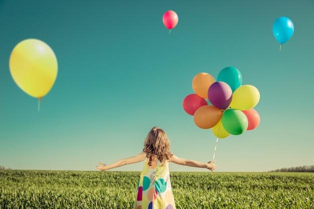 Glückliches kind, das mit bunten spielzeugballons draußen spielt. lächelndes kind, das spaß im grünen frühlingsfeld gegen hintergrund des blauen himmels hat. freiheitskonzept Premium Fotos