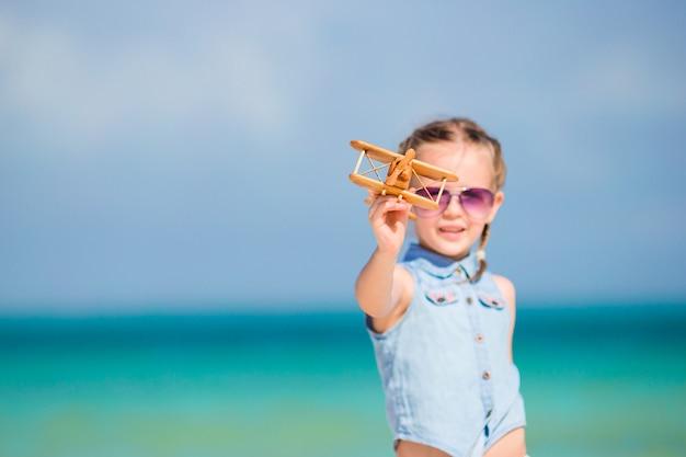 Glückliches kind, das mit spielzeugflugzeug auf dem strand spielt. Premium Fotos