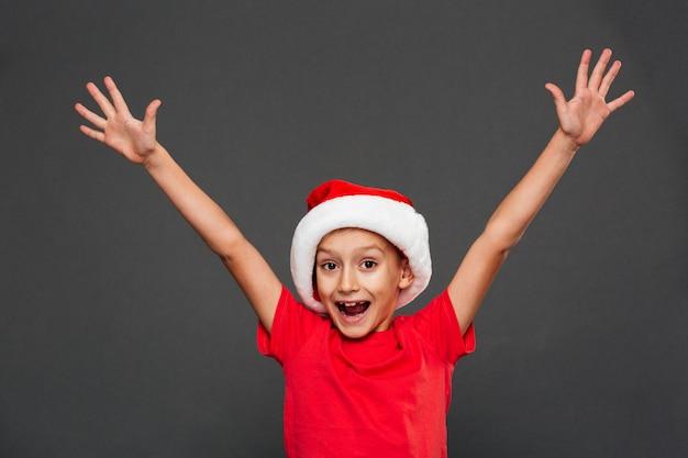 Glückliches kind des kleinen jungen, das weihnachtssankt-hut trägt Kostenlose Fotos