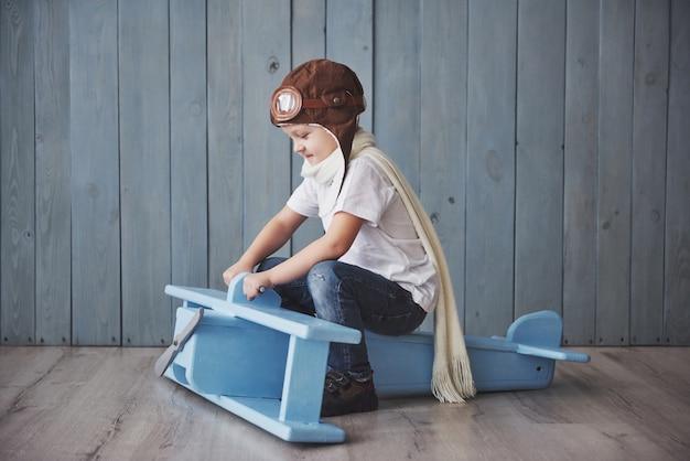Glückliches kind im versuchshut, der mit hölzernem flugzeug gegen spielt. kindheit. fantasie, vorstellungskraft. urlaub Premium Fotos