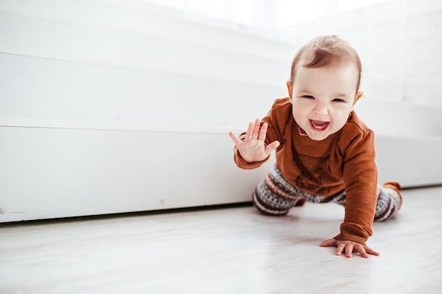 Glückliches kind in der orange strickjacke spielt mit feder auf dem boden Kostenlose Fotos