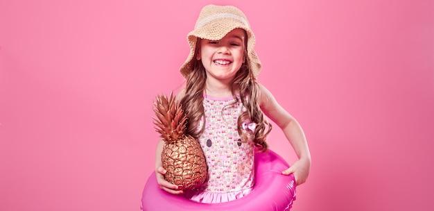 Glückliches kind mit ananas auf farbigem hintergrund Kostenlose Fotos