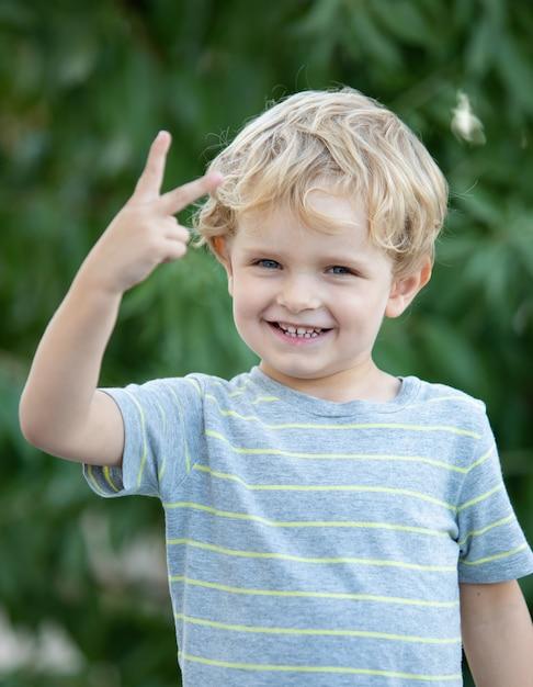 Glückliches kind mit blauem t-shirt im garten Premium Fotos