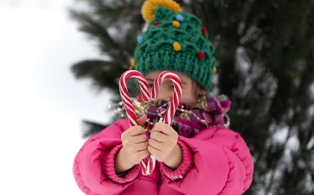 Glückliches kind mit großen zuckerstangen unter einem weihnachtsbaum. winterferienkonzept. Kostenlose Fotos