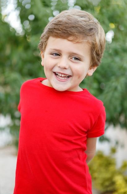 Glückliches kind mit rotem t-shirt im garten Premium Fotos
