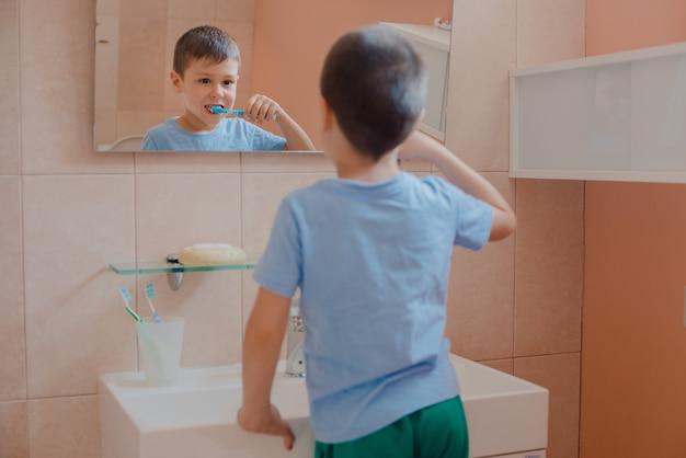 Glückliches kind oder kind, das zähne im badezimmer putzt. Premium Fotos