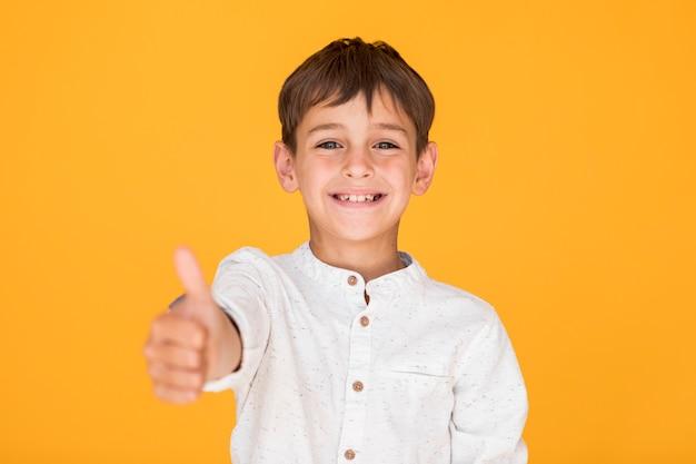 Glückliches kind, welches das gleiche zeichen zeigt Kostenlose Fotos