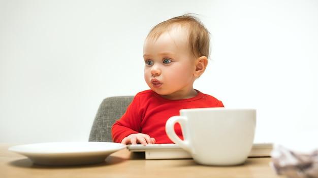 Glückliches kindbaby, das mit tastatur des modernen computers oder des laptops in weiß sitzt Kostenlose Fotos