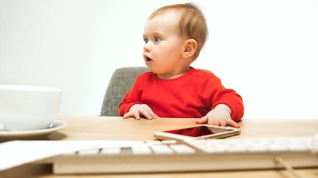 Glückliches kindbaby-kleinkind, das mit tastatur des computers lokalisiert auf einem weißen sitzt Kostenlose Fotos