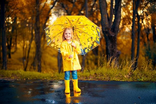 Glückliches kindermädchen mit einem regenschirm und gummistiefeln ein herbstweg Premium Fotos