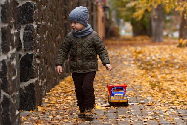 Glückliches kinderporträt mit spielzeugauto auf gelbem herbst. kleiner lächelnder junge, der mit großem spielzeugauto in der herbststadtstraße geht und spaß hat Premium Fotos