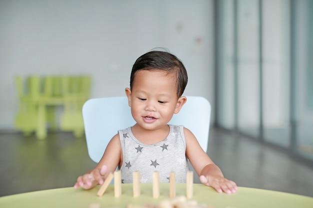Glückliches kleines asiatisches baby, das turmspiel der hölzernen blöcke für fähigkeit des gehirns und der körperlichen entwicklung in einem klassenzimmer spielt. fokus auf kindergesicht. kid phantasie und lernkonzept. Premium Fotos