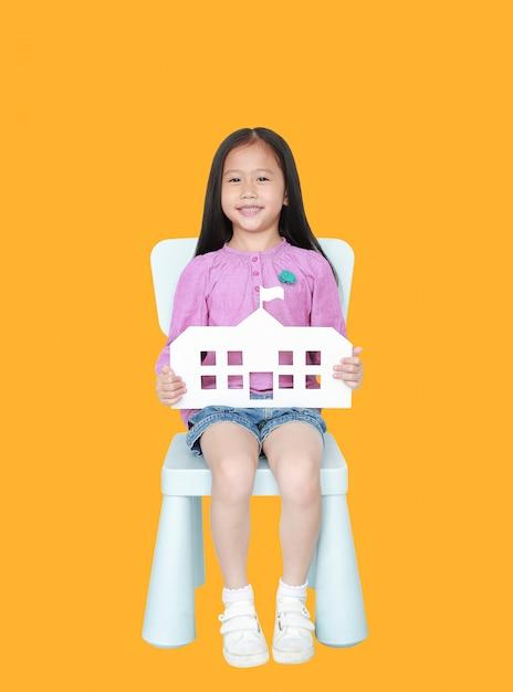 Glückliches kleines asiatisches kindermädchen, welches die papierschule sitzt auf kinderstuhl hält Premium Fotos
