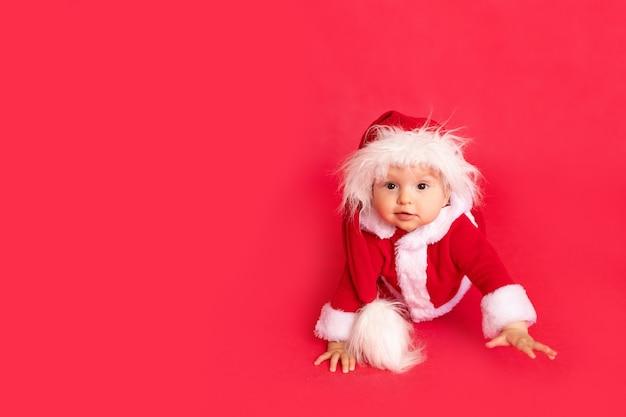Glückliches kleines baby im weihnachtsmannkostüm, das auf rot lokalisiert krabbelt Premium Fotos