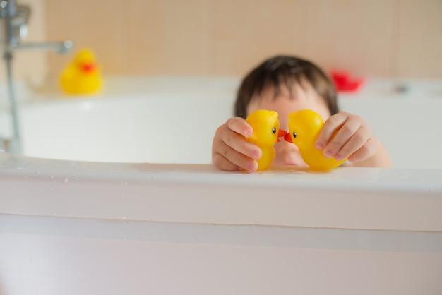 Glückliches kleines babybadezimmer, das mit gelben gummipunkten spielt. hygiene und pflege für kleine kinder. Premium Fotos