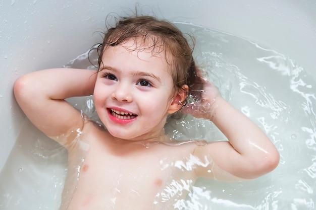 Glückliches kleines babygesichtsschwimmen im badezimmer. Premium Fotos