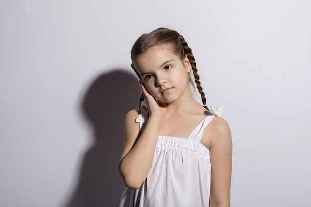 Glückliches kleines kaukasier des kleinen mädchens, das am telefon über weißem hintergrund spricht Premium Fotos