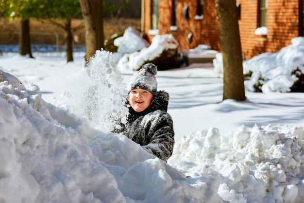 Glückliches kleines lächelndes mädchen draußen im schnee in der winterkleidung Premium Fotos