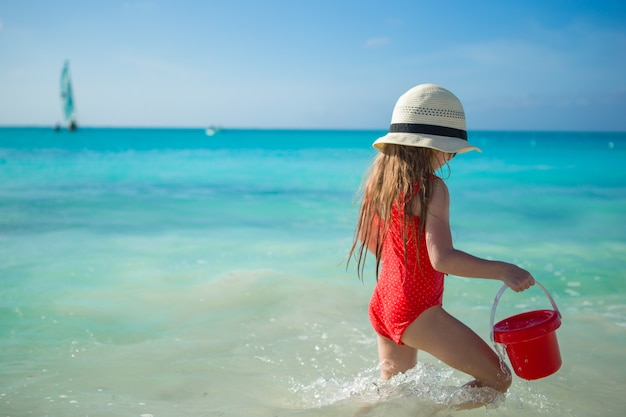 Glückliches kleines mädchen, das am strand während der karibischen ferien spielt Premium Fotos