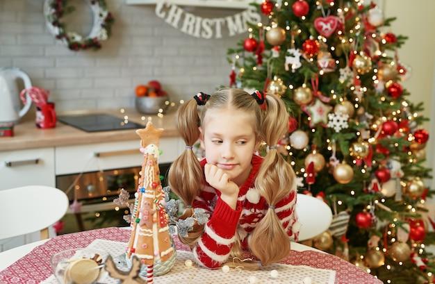 Glückliches kleines mädchen, das am tisch in der häuslichen küche mit weihnachtsbaum sitzt Premium Fotos