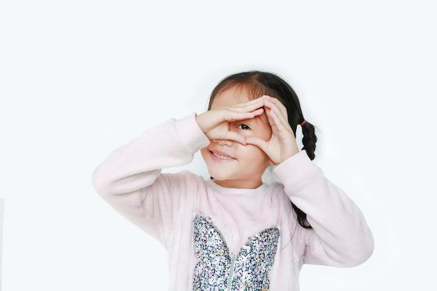 Glückliches kleines mädchen, das dreieck mit blick durch ihre hände lokalisiert macht. Premium Fotos