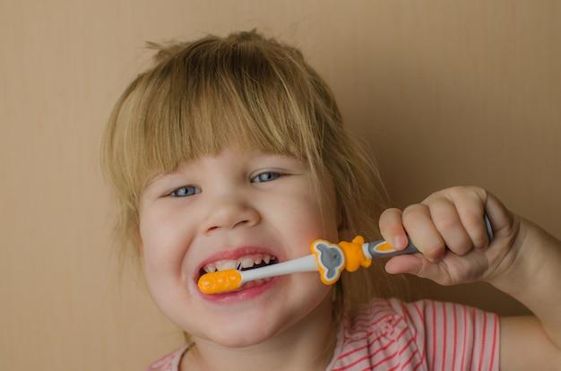 Glückliches kleines mädchen, das ihre zähne putzt. platz kopieren Premium Fotos