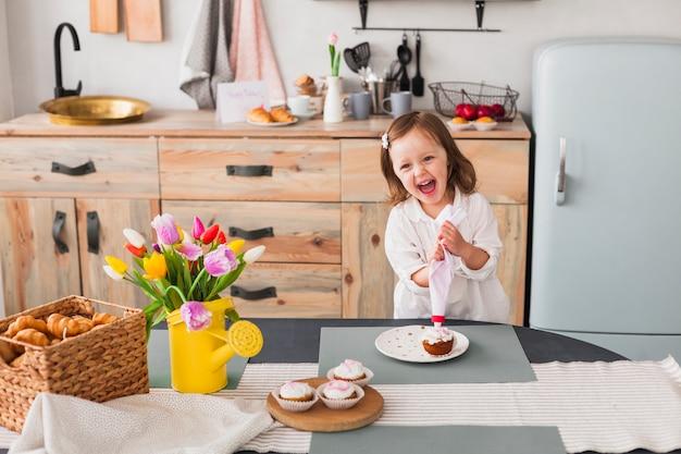 Glückliches kleines mädchen, das kleinen kuchen macht Kostenlose Fotos