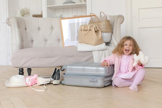 Glückliches kleines mädchen, das mit einem retro- koffer spielt Premium Fotos