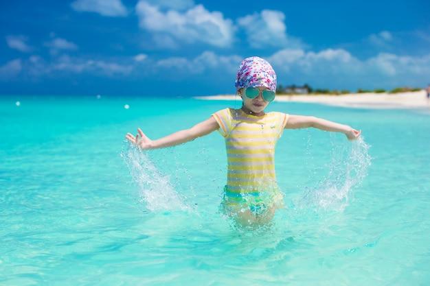 Glückliches kleines mädchen haben spaß am strand während der karibischen ferien Premium Fotos