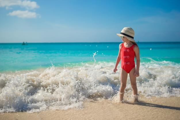 Glückliches kleines mädchen im hut am strand während der karibischen ferien Premium Fotos