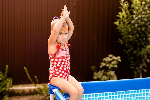 Glückliches kleines mädchen im roten badeanzug, der zu hause in swimmingpool im freien springt. baby, das lernt zu schwimmen. wasserspaß für kinder. Premium Fotos