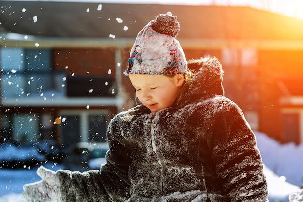 Glückliches kleines mädchen in den weißen handschuhen gehend in den winterpark wirft schnee oben Premium Fotos