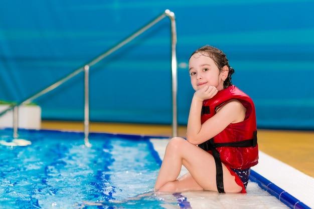 Glückliches kleines mädchen in einer roten weste, die auf den schritten des pools im wasserpark sitzt Premium Fotos