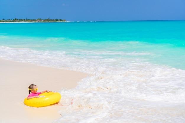 Glückliches kleines mädchen mit dem aufblasbaren gummikreis, der spaß auf dem strand im seichten wasser hat Premium Fotos