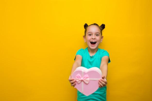 Glückliches kleines mädchen mit den endstücken, die über der gelben wand hält kaufende rosa tasche lokalisiert stehen. lächelt nachdenklich Premium Fotos