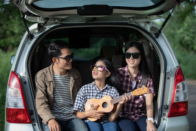 Glückliches kleines mädchen mit der asiatischen familie, die im auto sitzt Premium Fotos