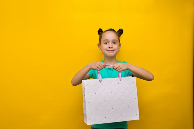 Glückliches kleines mädchen mit der lustigen endstückstellung lokalisiert über der gelben wand, die einkaufstaschen hält. kamera suchen Premium Fotos