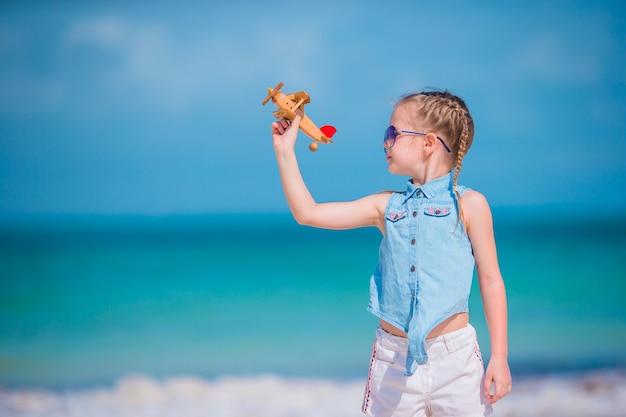 Glückliches kleines mädchen mit spielzeugflugzeug in den händen am weißen sandstrand. kind spielen mit spielzeug am strand Premium Fotos
