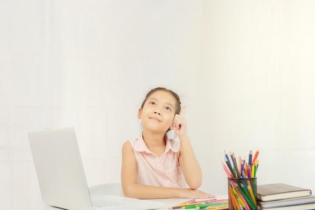 Glückliches kleines mädchen sitzt am tisch und denkt Premium Fotos