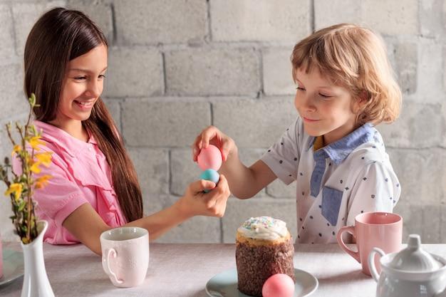 Glückliches kleines mädchen und junge, die traditionelles osterspiel spielen - ei, das mit farbigen eiern zu hause klopft Premium Fotos