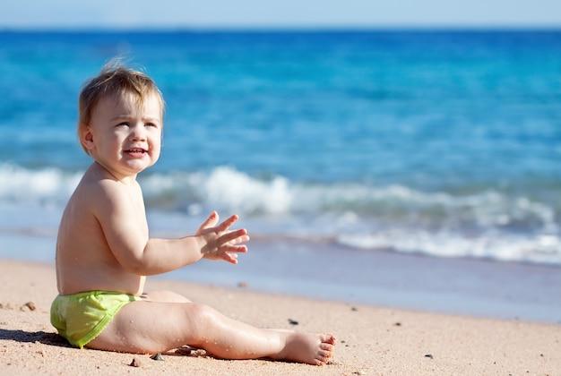 Glückliches kleinkind am sandstrand Kostenlose Fotos
