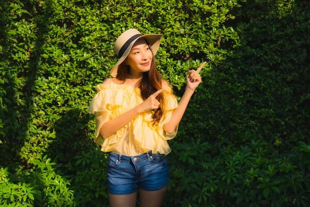 Glückliches lächeln der jungen asiatischen frau des porträts entspannen sich um naturgarten im freien Kostenlose Fotos