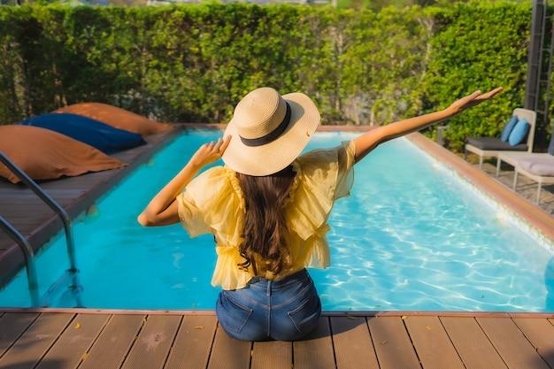 Glückliches lächeln der jungen asiatischen frau des porträts entspannen sich um swimmingpool im freien Kostenlose Fotos