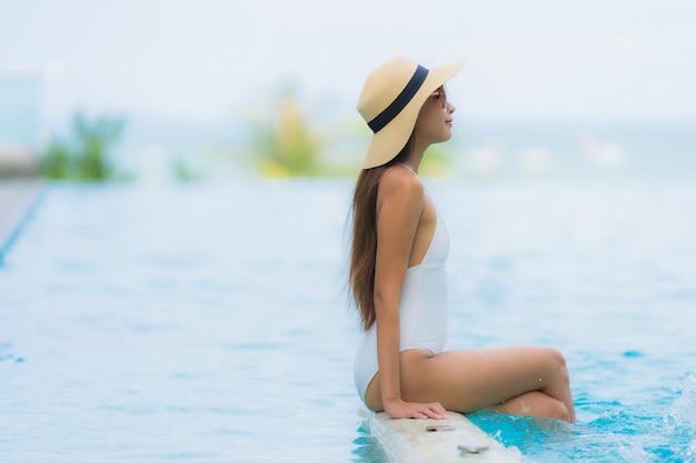 Glückliches lächeln der jungen asiatischen frau des porträts entspannen sich um swimmingpool im hotelerholungsort Kostenlose Fotos