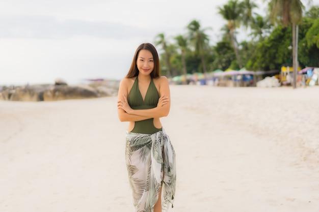 Glückliches lächeln der schönen asiatischen frauen des porträts entspannen sich auf dem tropischen strandseeozean Kostenlose Fotos