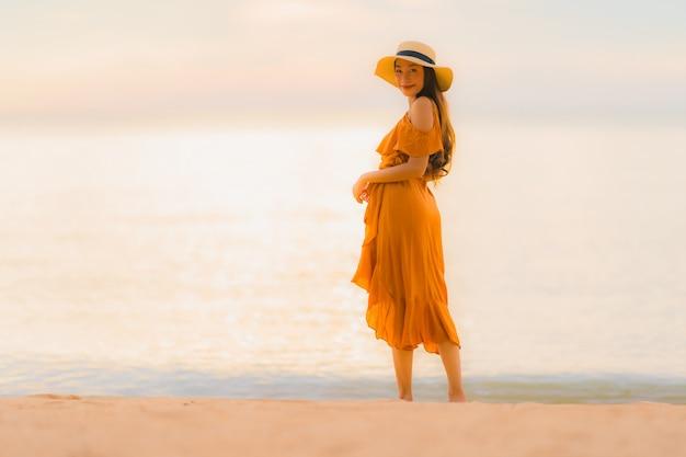Glückliches lächeln der schönen jungen asiatischen frau des porträts entspannen sich auf dem strandseeozean Kostenlose Fotos