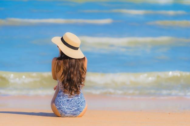 Glückliches lächeln der schönen jungen asiatischen frau des porträts entspannen sich auf dem tropischen strandseeozean für freizeitreise Kostenlose Fotos